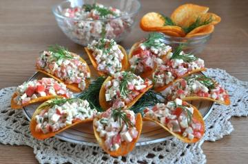 Salad appetizer with crab sticks on chips for the New Year